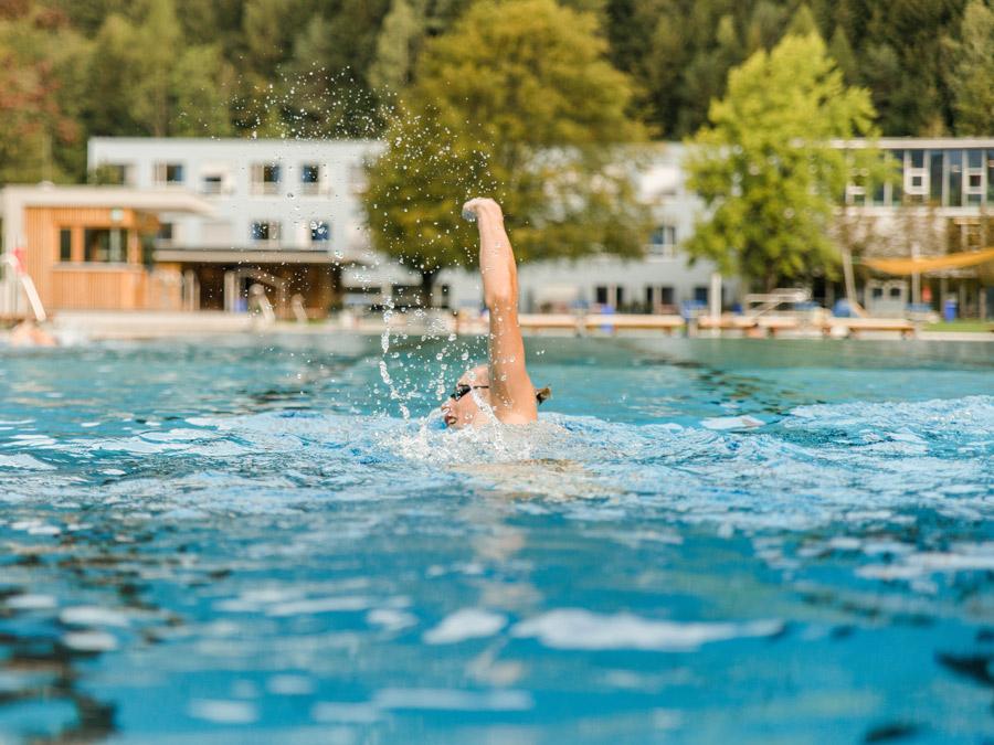 Frau schwimmt im Freibad