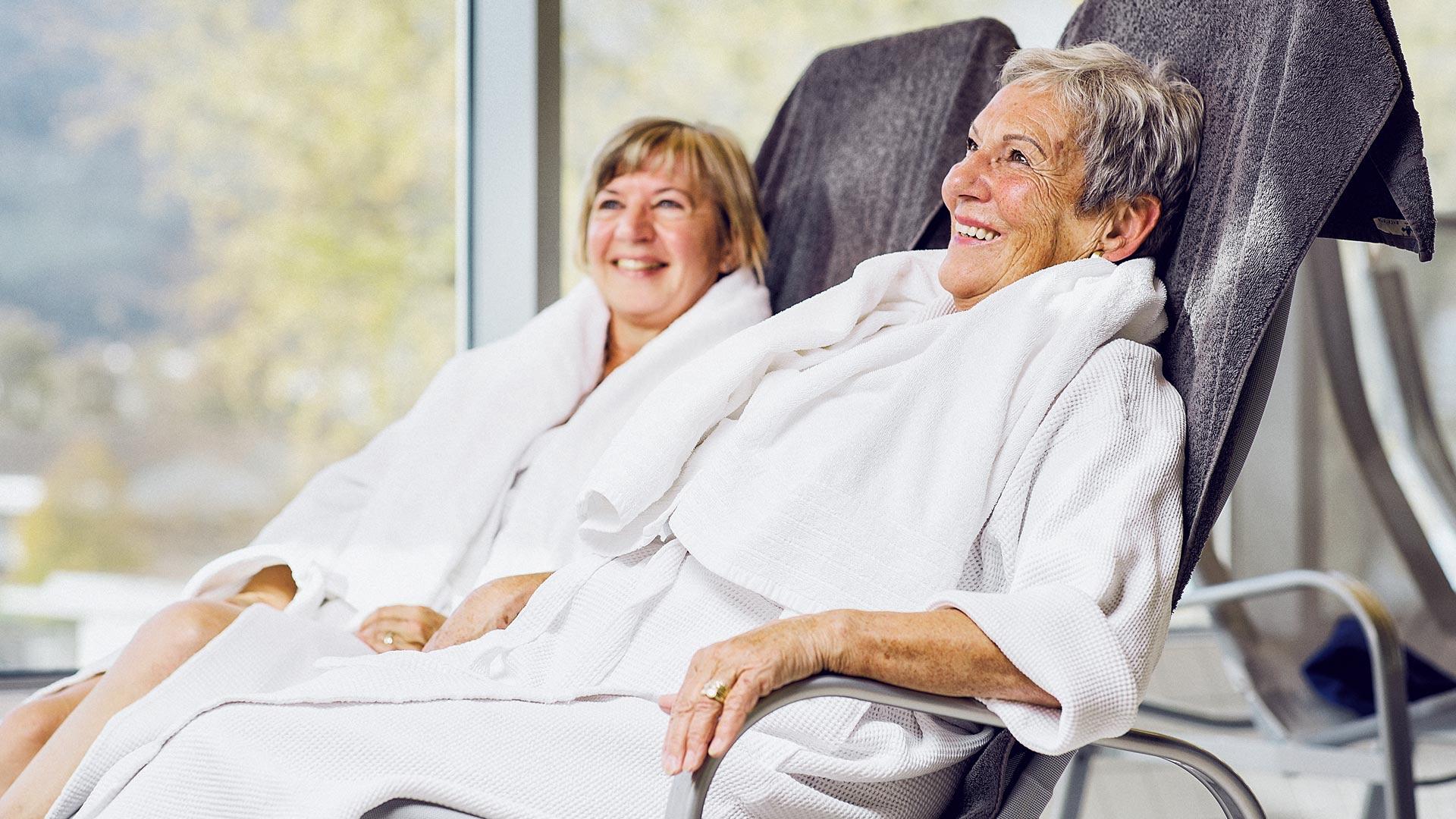 Pensionisten mit Bademänteln in Stühlen